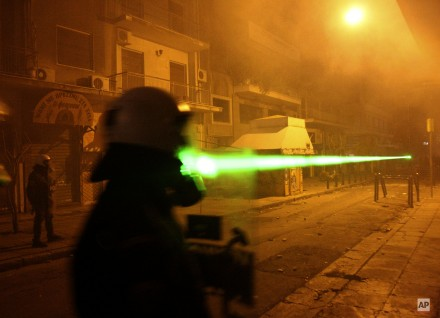 Protesters, unseen, use an aim laser pointer to a riot police officer during clashes between protesters and riot police in Athens, Saturday, Dec. 13, 2008. Protesters remain on the streets of Greece, one week after the police shot dead 15-year-old Alexandros Grigoropoulos which sparked massive riots. (AP Photo/Petros Karadjias)