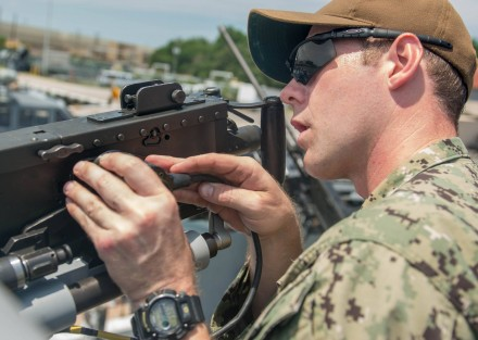 NORFOLK (July 25, 2017) Electronics Technician 1st Class Gary Holton inspects an M2HB machine gun before Coastal Riverine Squadron 4 goes on an evening training patrol. CRS-4 is currently conducting a training cycle in preparation for a future deployment. (U.S. Navy photo by Mass Communication Specialist 1st Class Patrick Enright/Released)